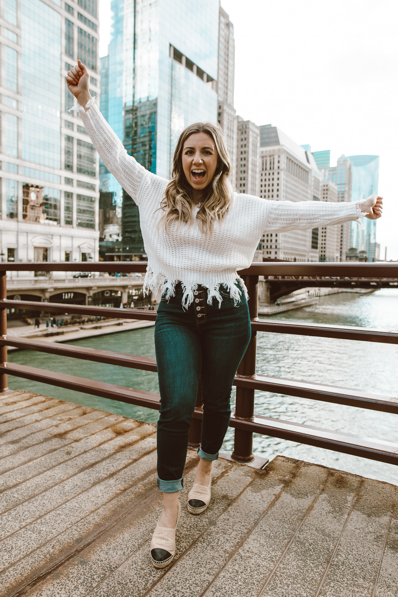 Neutral Colors by popular Chicago fashion blog, Glass of Glam: image of a woman standing outside in downtown Chicago and wearing a Neutral Rebel On the Edge Fringe Sweater, Chanel espadrilles, Neutral Rebel Kancan High-Rise Skinny Jeans in Dark Blue, and Etsy name necklace.