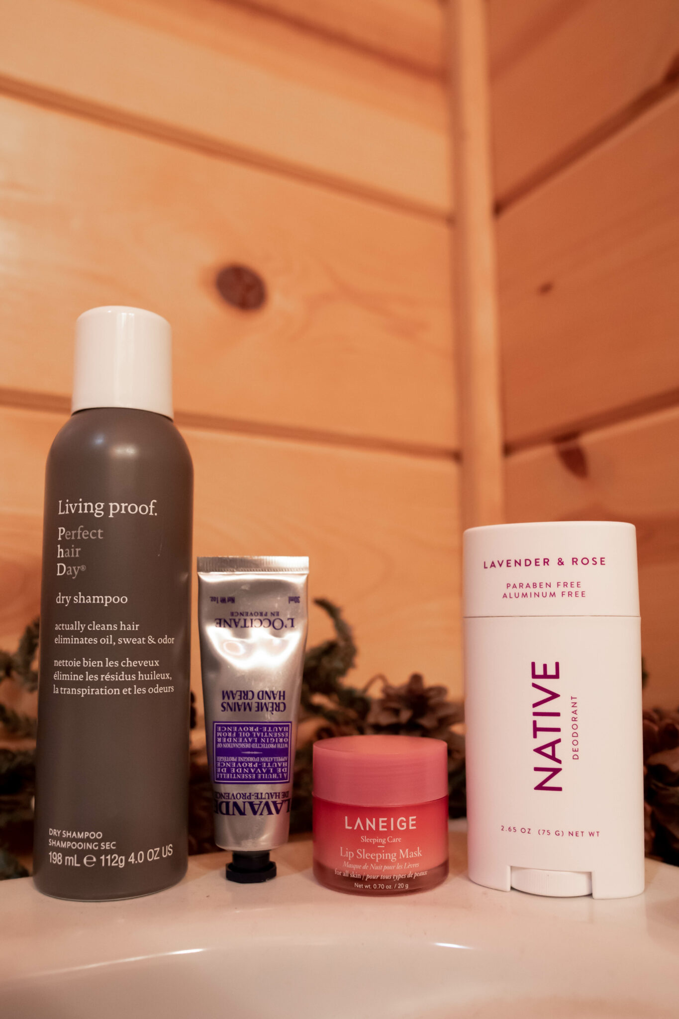 Cabin Beauty Essentials by popular Chicago beauty blog, Glass of Glam: image of Living Proof dry shampoo, Native deodorant, Laneige lip sleeping mask, and L'occitane hand cream.