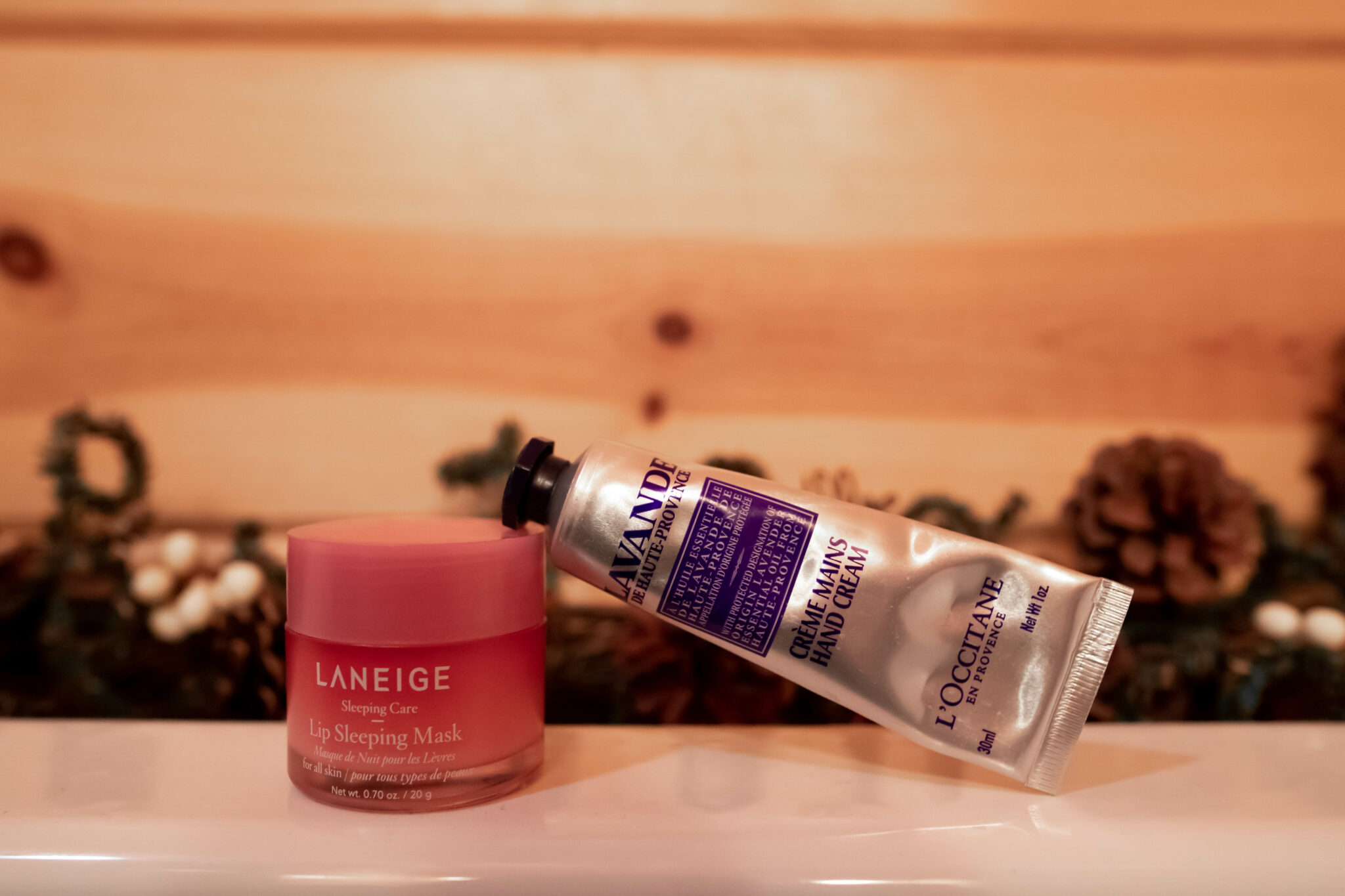 Cabin Beauty Essentials by popular Chicago beauty blog, Glass of Glam: image of Laneige lip sleeping mask and L'occitane hand cream.