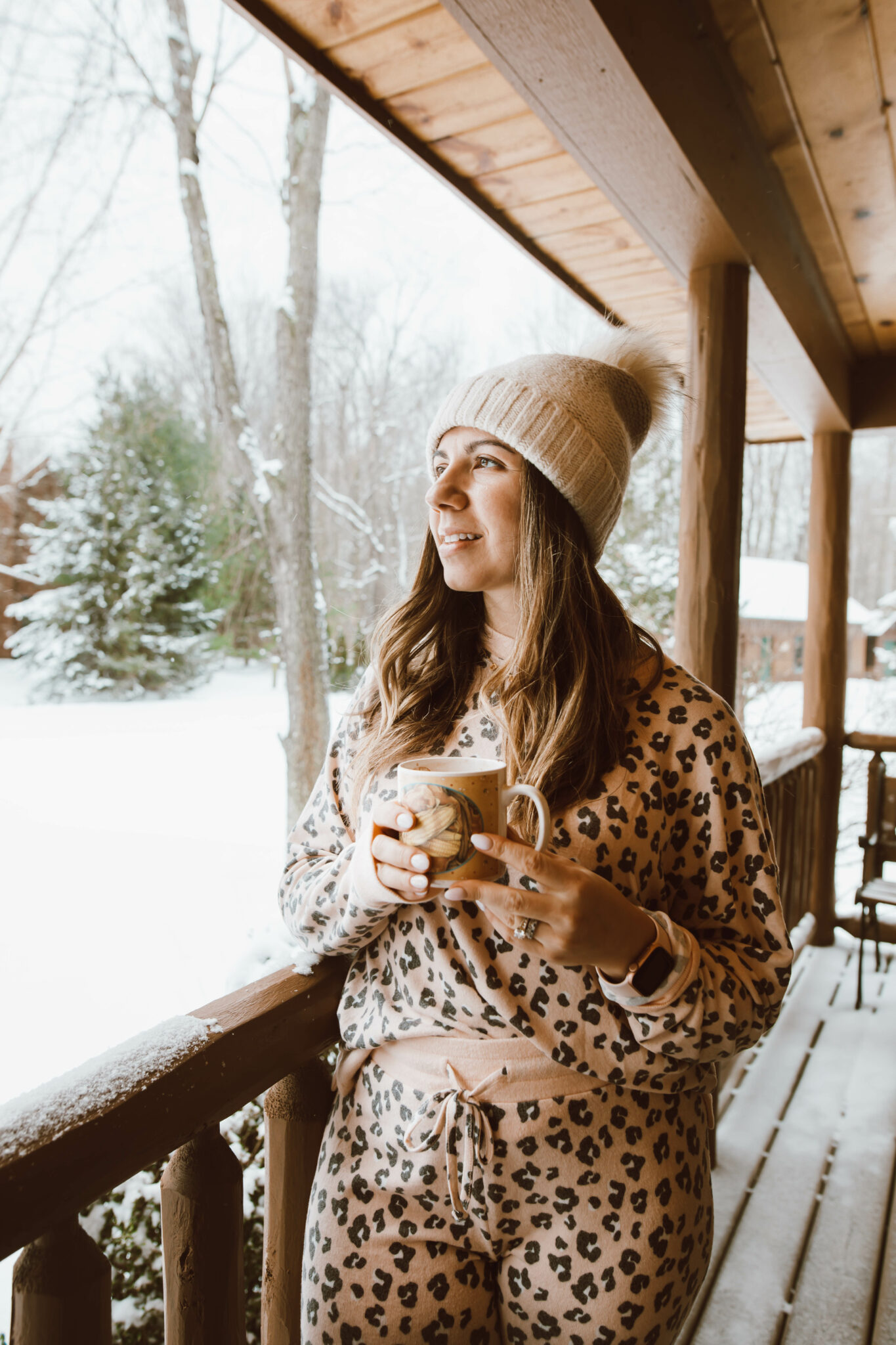 Loungewear Set by popular Chicago fashion blog, Glass of Glam: image of a woman standing on a cabin deck and wearing a leopard print loungewear set and cream pom beanie.
