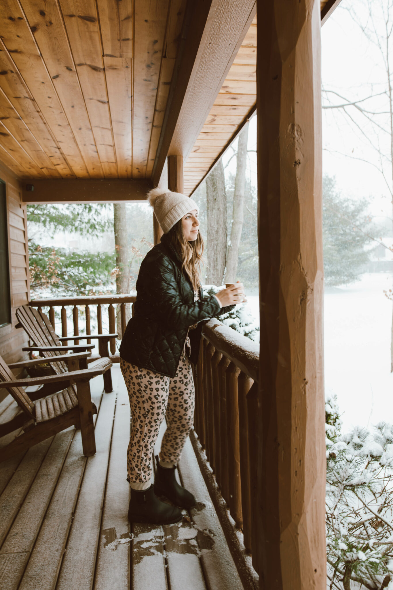 Loungewear Set by popular Chicago fashion blog, Glass of Glam: image of a woman standing on a cabin deck and wearing a leopard print loungewear set, quilted jacket and cream pom beanie.