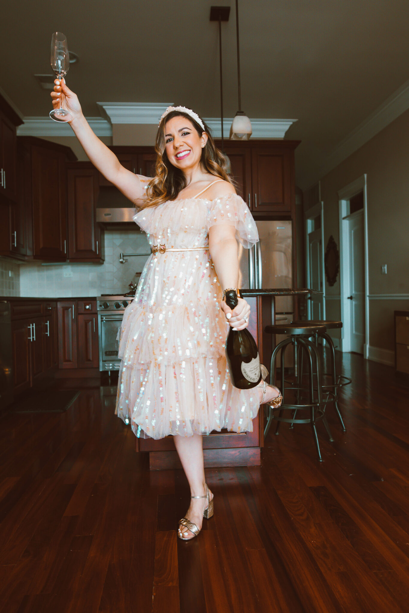 Party Dress by popular Chicago fashion blog, Glass of Glam: image of a woman holding a champagne flute and wearing a sequin party dress, pearl embellished knot headband, and Gucci block heel sandals.