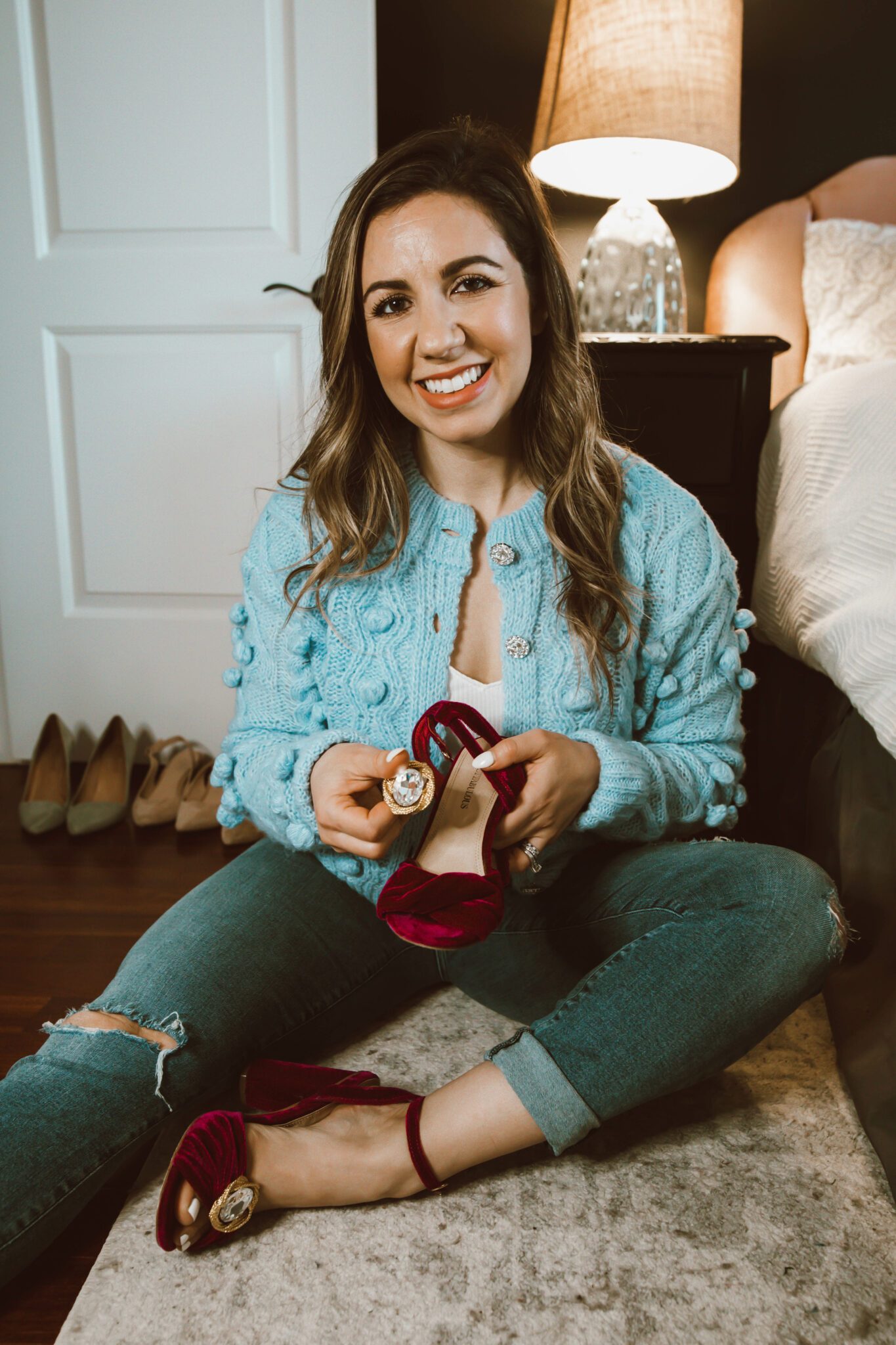 Clip On Earrings by popular Chicago fashion blog, Glass of Glam: image of a woman sitting on her bedroom floor and putting gold clip on earrings on her wine colored velvet sandals.