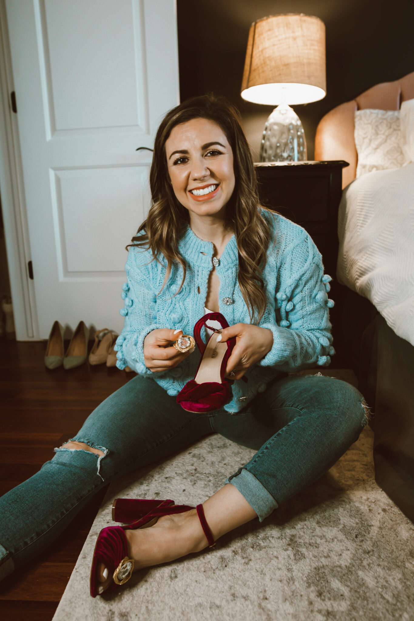 Clip On Earrings by popular Chicago fashion blog, Glass of Glam: image of a woman holding a pair of red velvet strappy block heel shoes with clip on earrings on them.