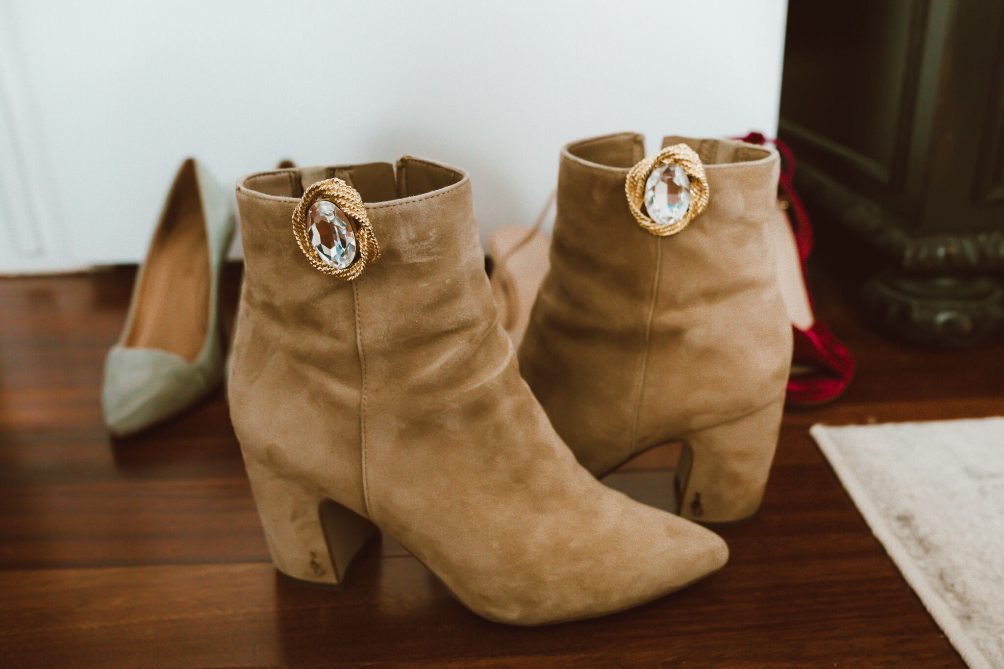 Clip On Earrings by popular Chicago fashion blog, Glass of Glam: image of brown suede ankle boots with clip on earrings attached to them.