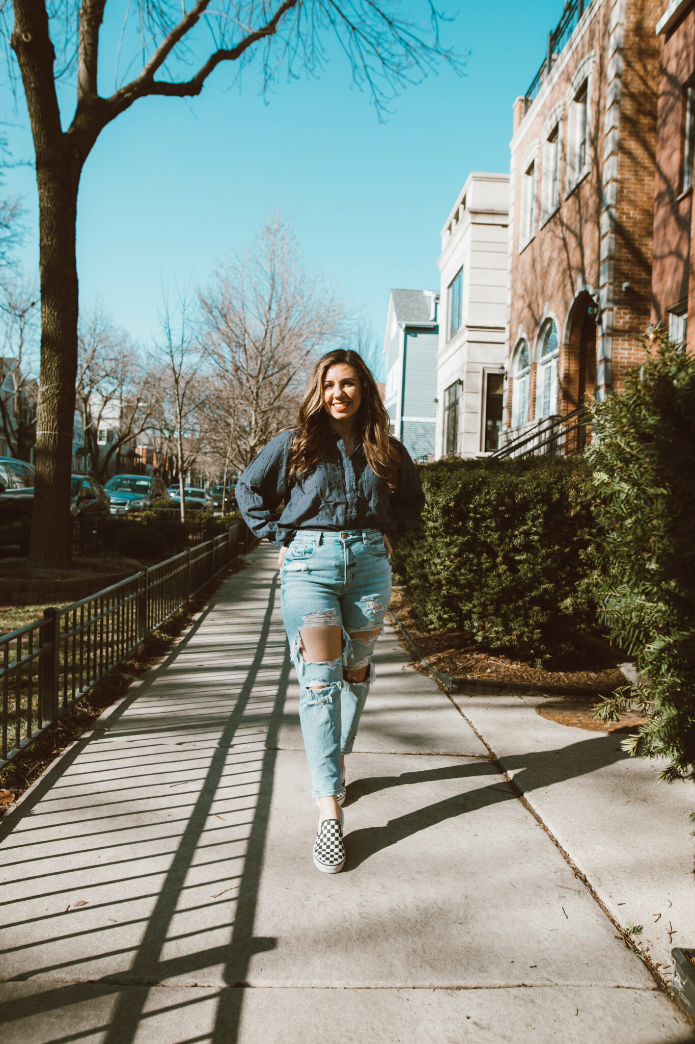Poet Blouse by popular Chicago fashion blog, Glass of Glam: image of a woman wearing a poet blouse, distressed denim and black and white checkered Vans sneakers.