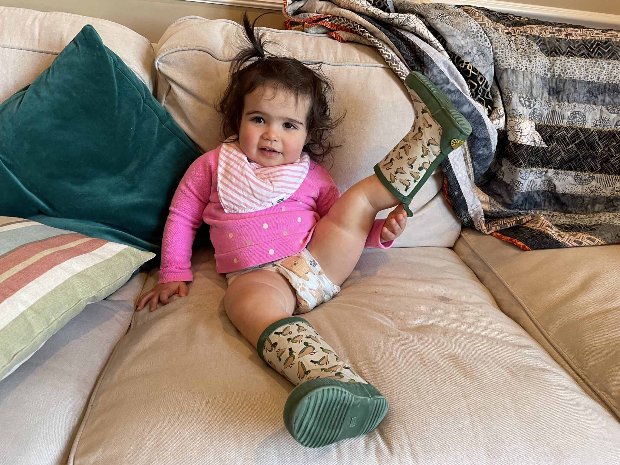 Life Update by popular Chicago lifestyle blog, Glass of Glam: image of a little girl sitting on a couch and wearing a pair of duck rain boots with a pink and gold dot long sleeve t-shirt and a pink and white stripe bandana bib.