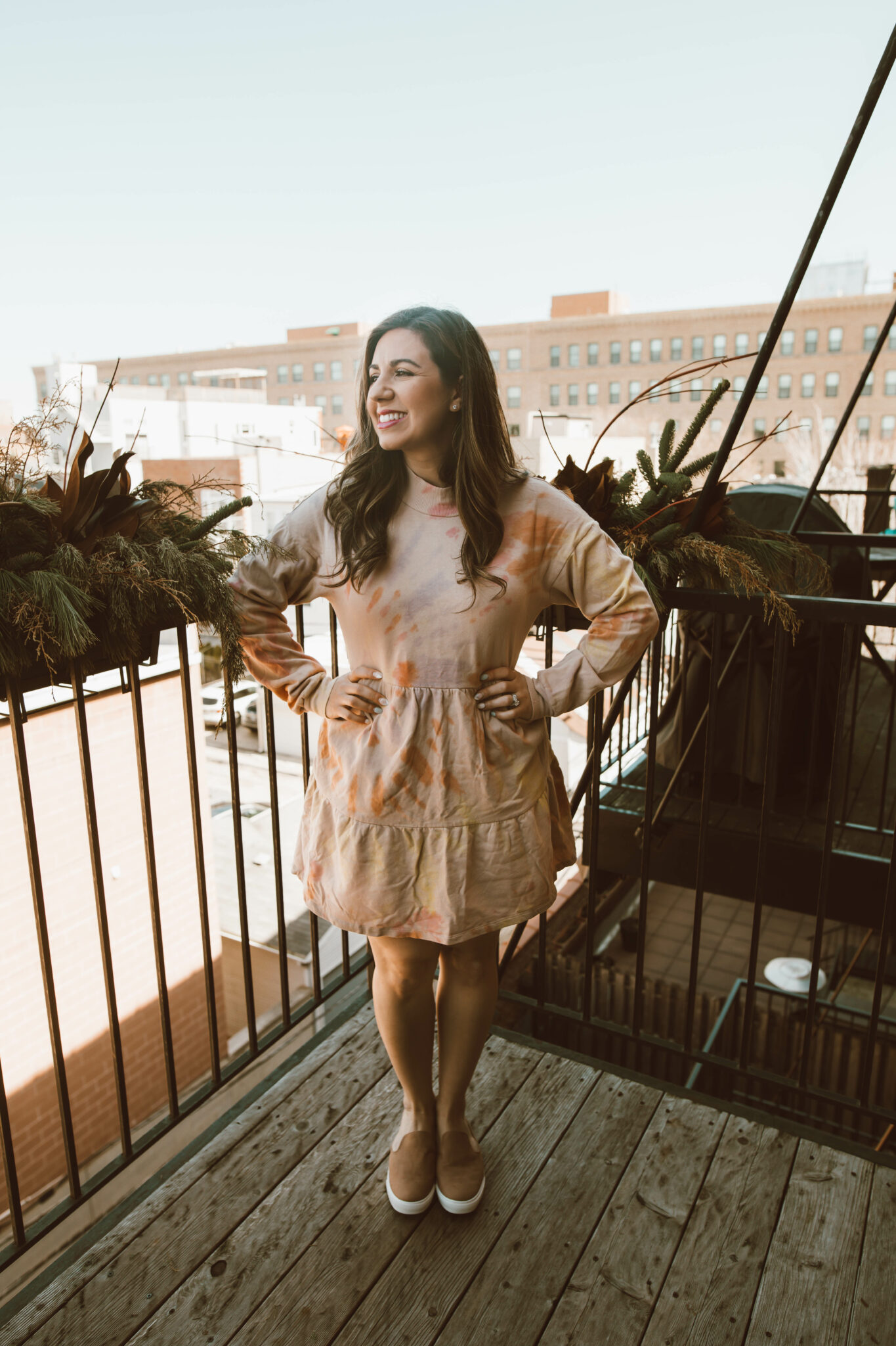 Tie Dye Dresses by popular Chicago fashion blog, Glass of Glam: image of a woman standing on her balcony and wearing a orange tie dye dress and brown slip on sneakers.