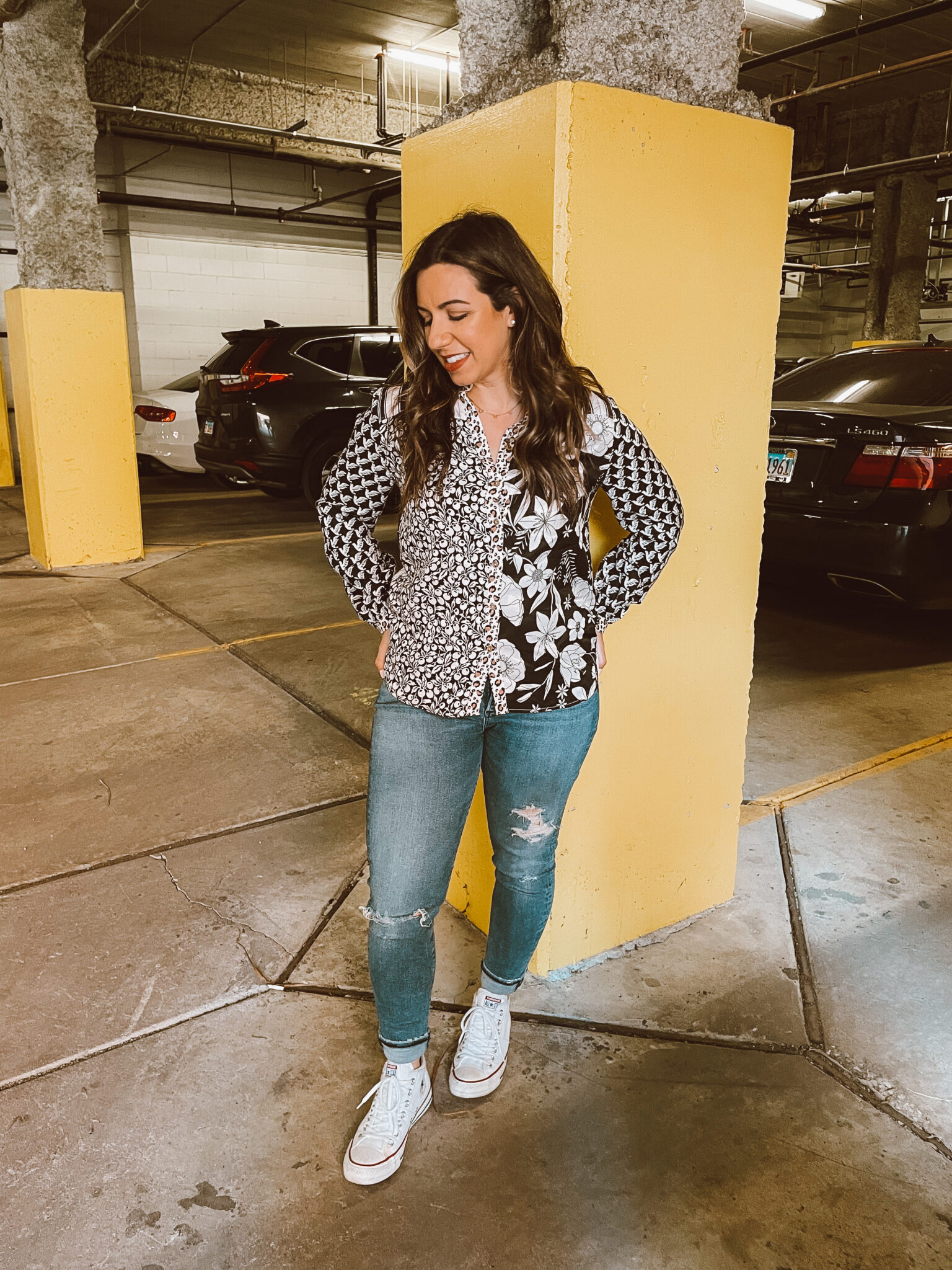 Tucked Shirt by popular Chicago fashion blog, Glass of Glam: image of a woman standing in a parking garage and wearing a black and white mixed print button up shirt, distressed denim, and white Converse sneakers.