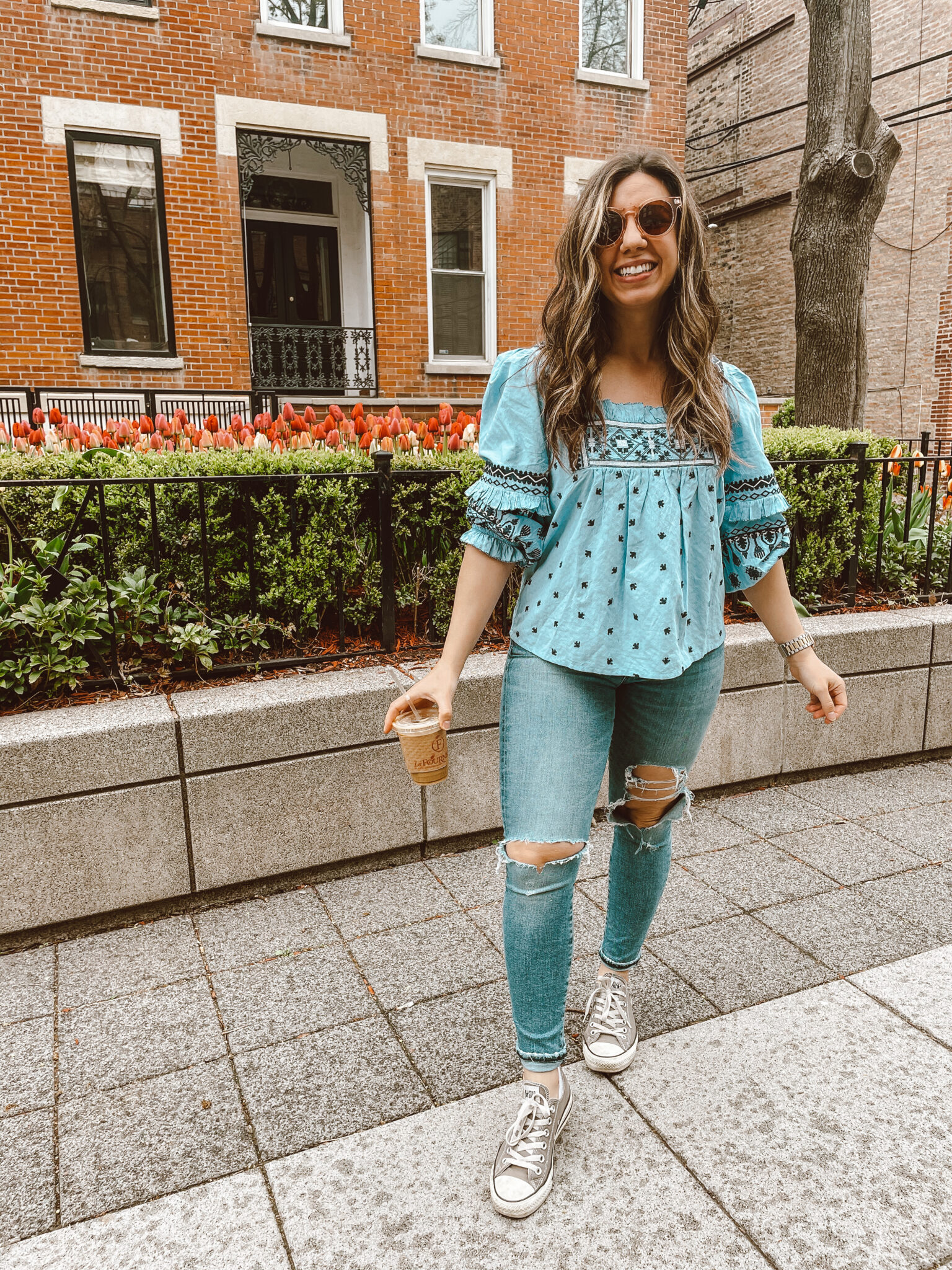 Square Neck Blouse by popular Chicago fashion blog, Glass of Glam: image of a woman standing outside and holding a iced coffee while wearing a blue embroidered blouse, distressed denim, and Converse sneakers.