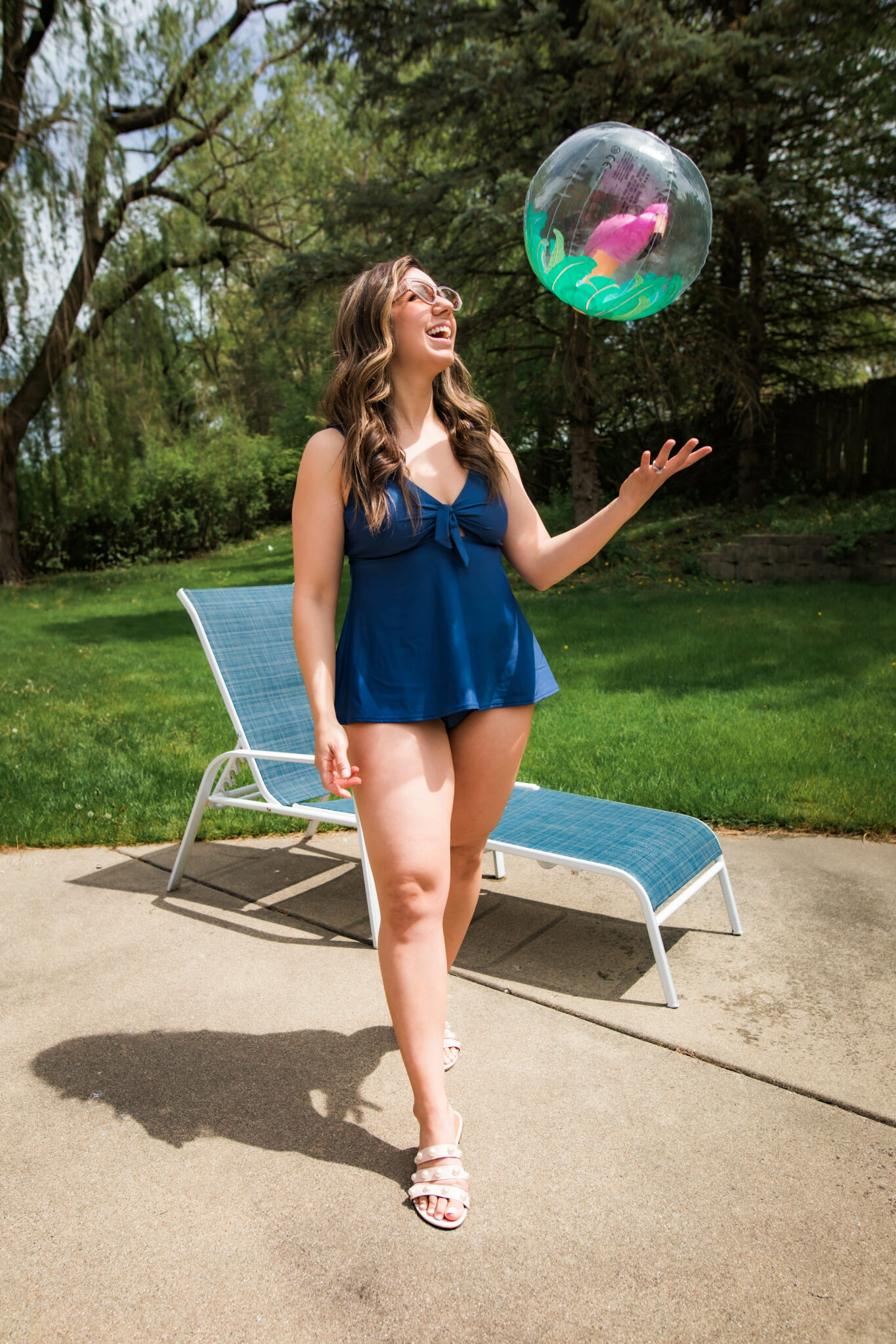 Best Swimsuits for Mom by popular Chicago fashion blog, Glass of Glam: image of a woman holding a beach ball and wearing a blue Bare Necessities two piece with white strap slide sandals.