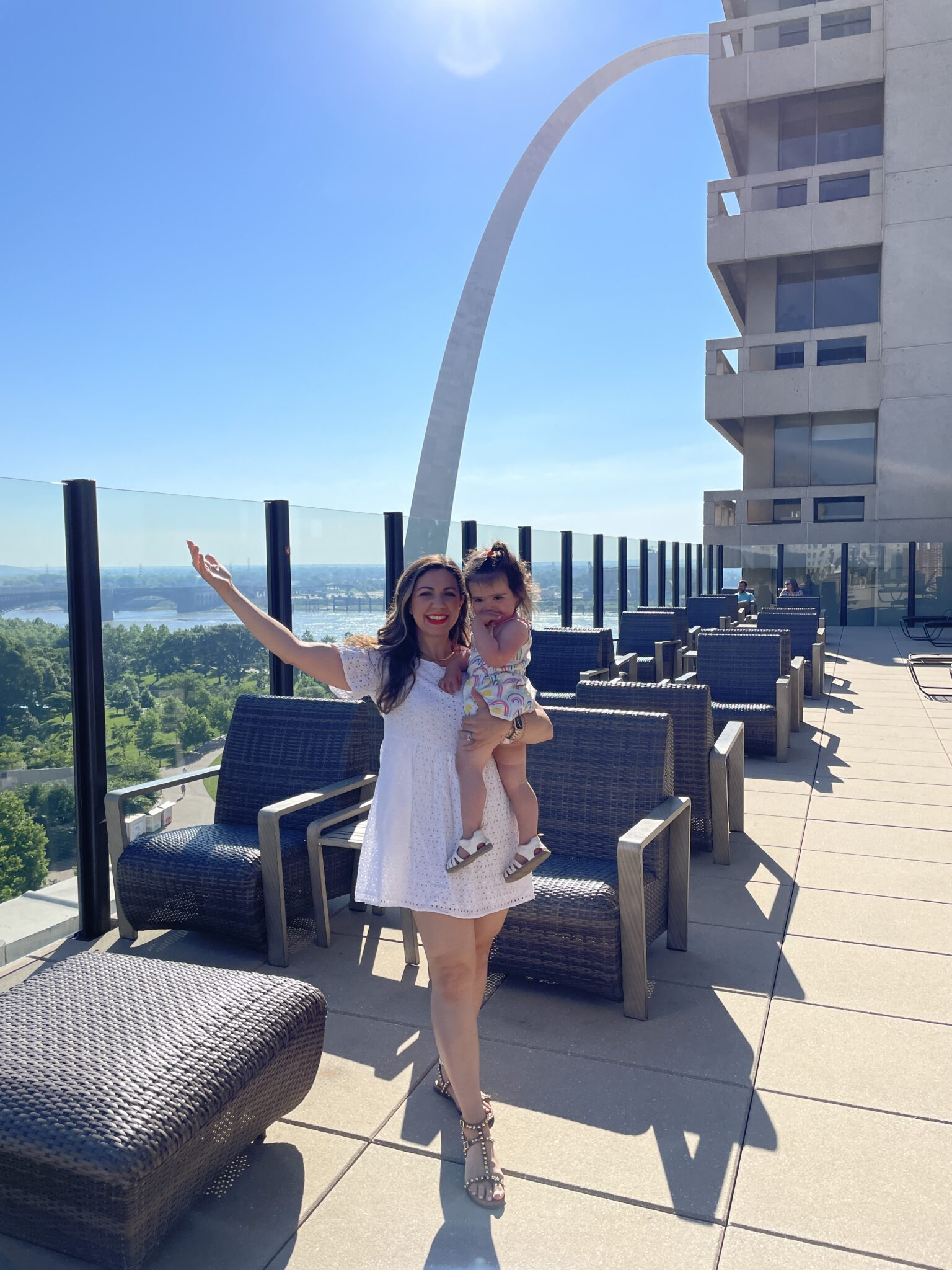 Traveling to St. Louis by popular Chicago travel blogger, Glass of Glam: image of a woman wearing a white dress and holding her young daughter while standing on a roof.