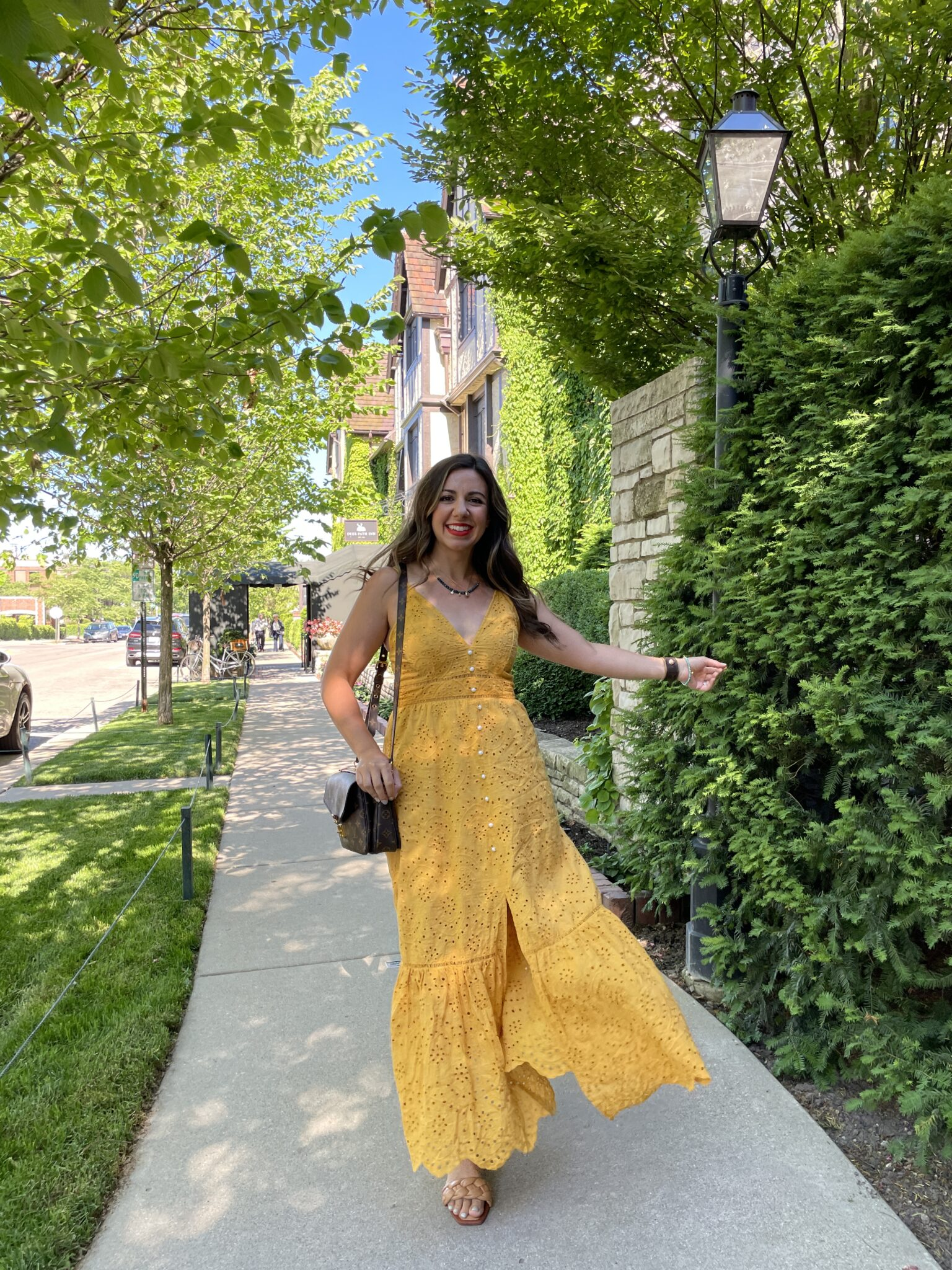 Eyelet Clothing by popular Chicago fashion blog, Glass of Glam: image of a woman walking outside next to a fence covered in ivy and wearing a yellow eyelet maxi dress with tan braided sandals and a silpada necklace.