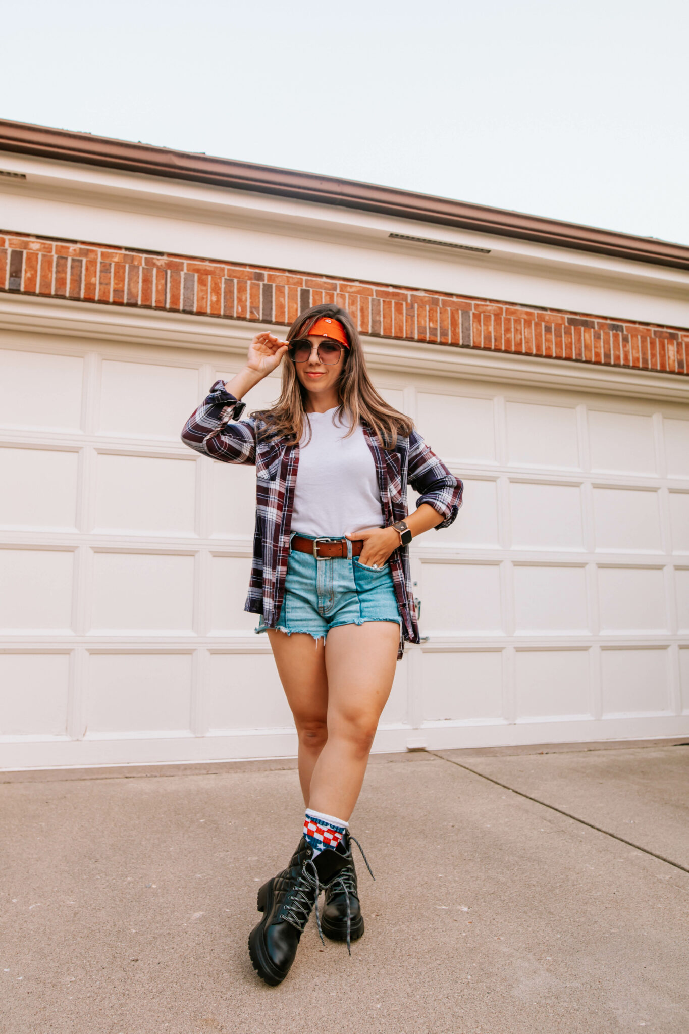 Grunge Clothing by popular Chicago fashion blog, Glass of Glam: image of a woman wearing a read bandana tied around her forehead, white t-shirt, distressed denim shorts, brown belt, plaid button up shirt, and black combat boots.