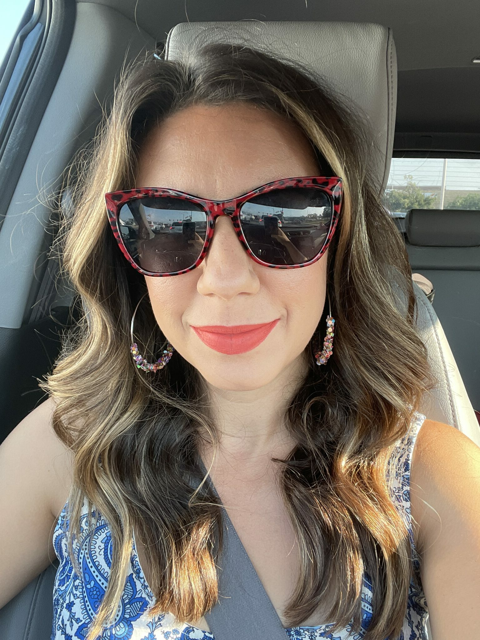 summer lipsticks | Summer Lipstick Colors by popular Chicago beauty blog, Glass of Glam: image of a woman wearing red tortoise shell sunglasses, red lipstick and a blue and white paisley top.