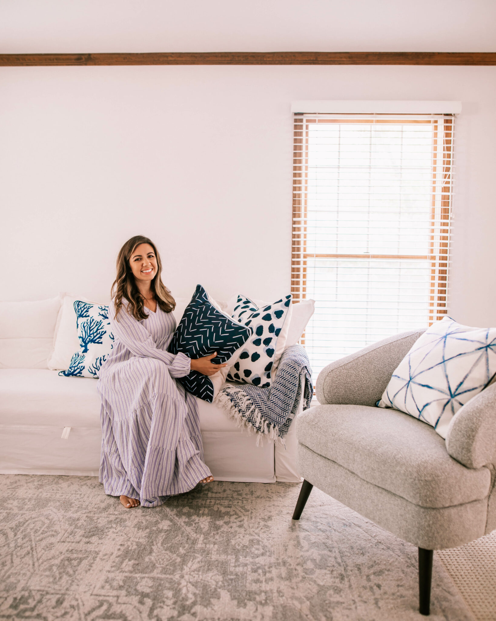 Thomasville Furniture by popular Chicago life and style blog, Glass of Glam: image of a woman wearing a purple stripe maxi dress and sitting in a living room decorated with a white couch, blue, grey and white accent rug, grey armchair, and blue and white throw pillows.
