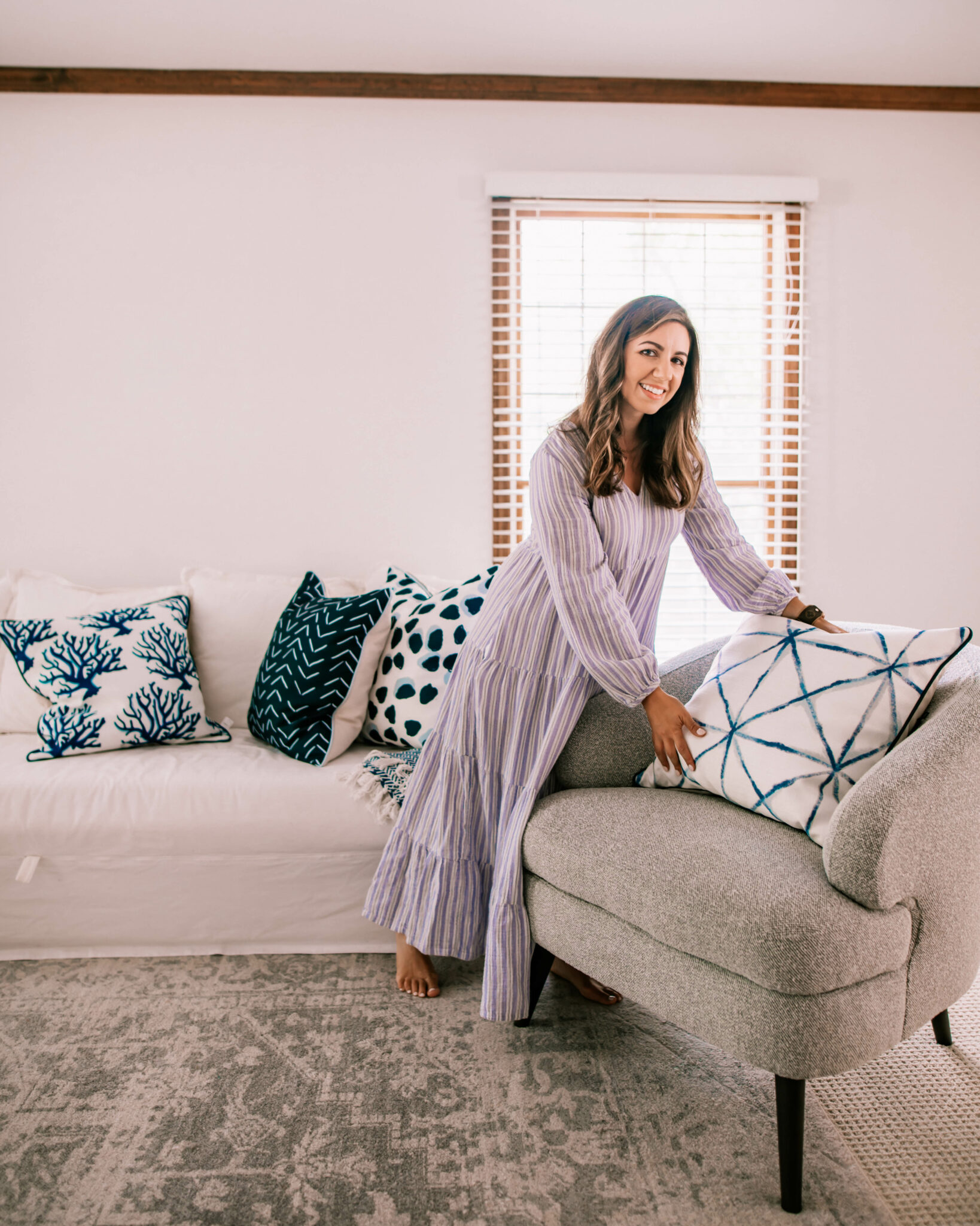 Thomasville Furniture by popular Chicago life and style blog, Glass of Glam: image of a woman wearing a purple stripe maxi dress and setting a white and blue throw pillow on a grey armchair.