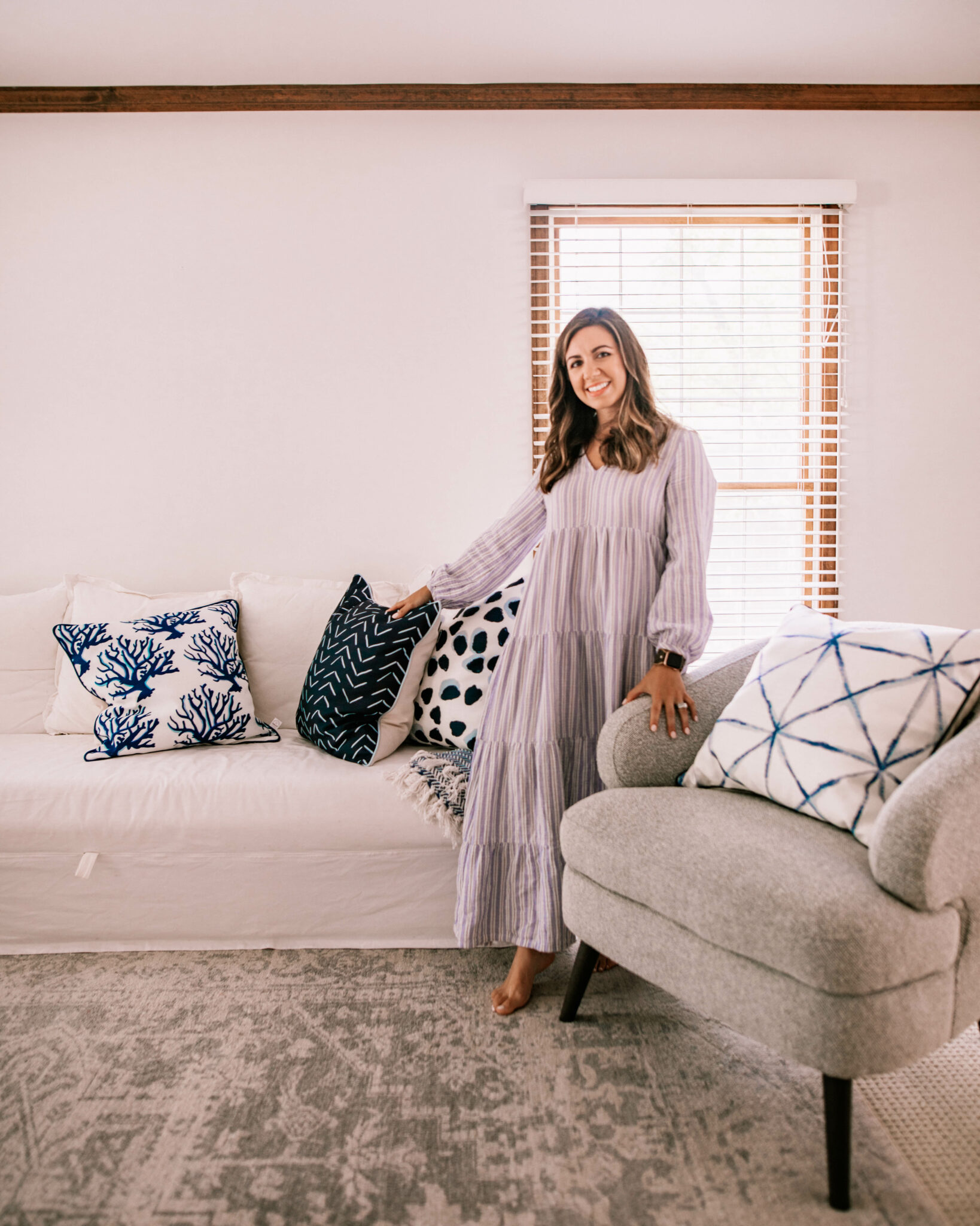 Thomasville Furniture by popular Chicago life and style blog, Glass of Glam: image of a woman wearing a purple stripe maxi dress and standing in a living room decorated with a white couch, blue, grey and white accent rug, grey armchair, and blue and white throw pillows.