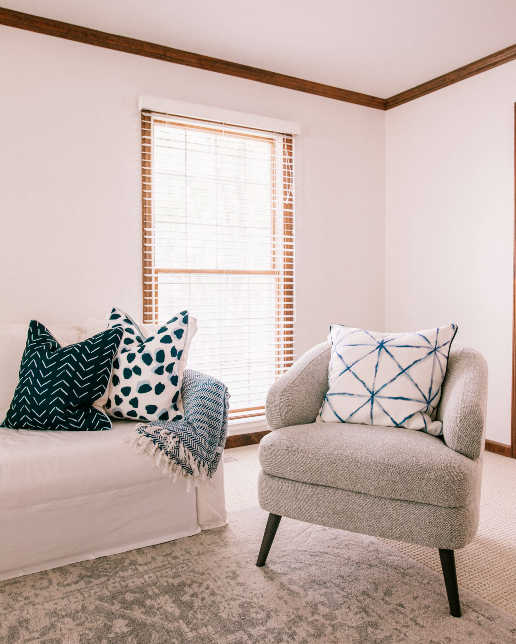 Thomasville Furniture by popular Chicago life and style blog, Glass of Glam: image of living room decorated with a white couch, blue, grey and white accent rug, grey armchair, and blue and white throw pillows.